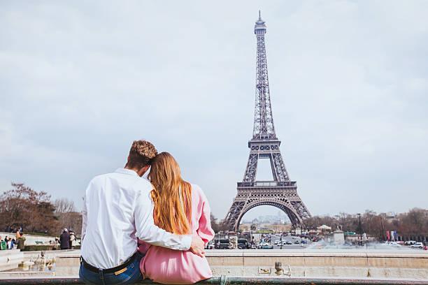 romantic couple looking at Eiffel tower in Paris, honeymoon background